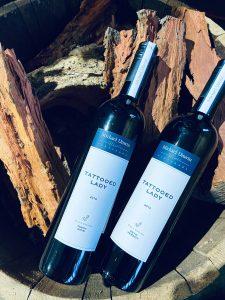 Two Tattooed Lady wine bottles in a barrel of wood